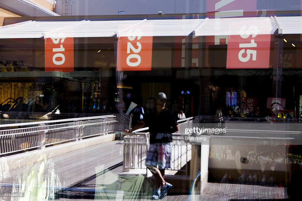 The reflection of a shopper is seen in the window of a Hennes & Mauritz AB (H&M) store at the Fashion Valley Mall in San Diego, California, U.S., on Saturday, June 22, 2013. The Bureau of Economic Analysis is schedule to release personal consumption figures on June 26. Photographer: Sam Hodgson/Bloomberg via Getty Images