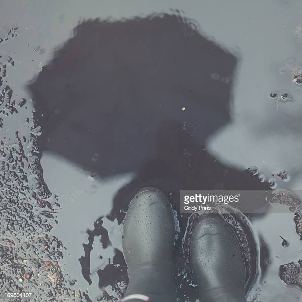 The reflection of an umbrella in a muddy puddle