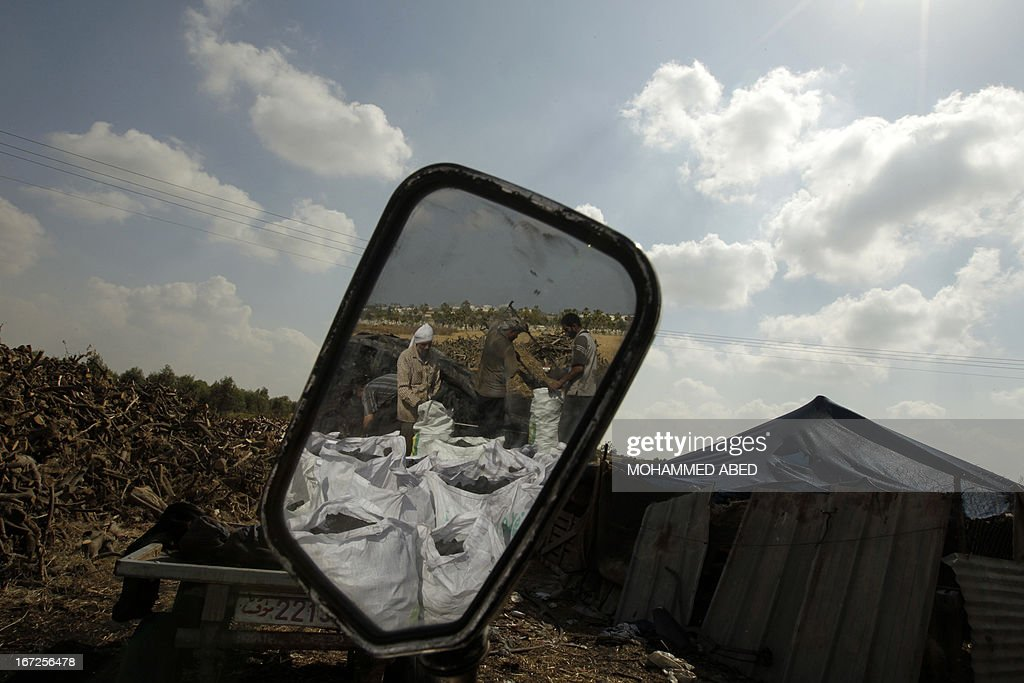 The reflection of Palestinian workers loading coal into bags is seen in the wing mirror of a vehicle at one of the few local charcoal manufacturing plants east of Gaza City on April 23, 2013.
