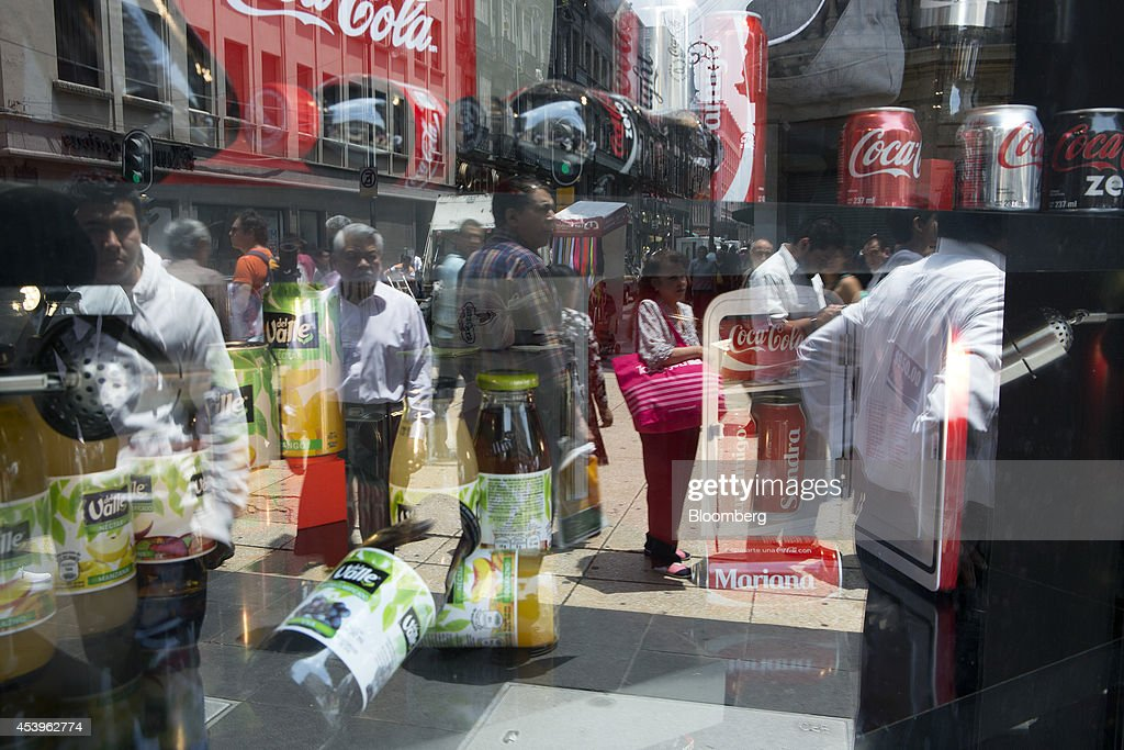 The reflection of pedestrians is seen in a window displaying Coca-Cola products in Mexico City, Mexico, on Thursday, Aug. 21, 2014. Mexican consumer prices rose more than analysts expected in the first half of August and the unemployment rate rose to 5.47 percent in July compared with 4.8 percent in June. Photographer: Susana Gonzalez/Bloomberg via Getty Images