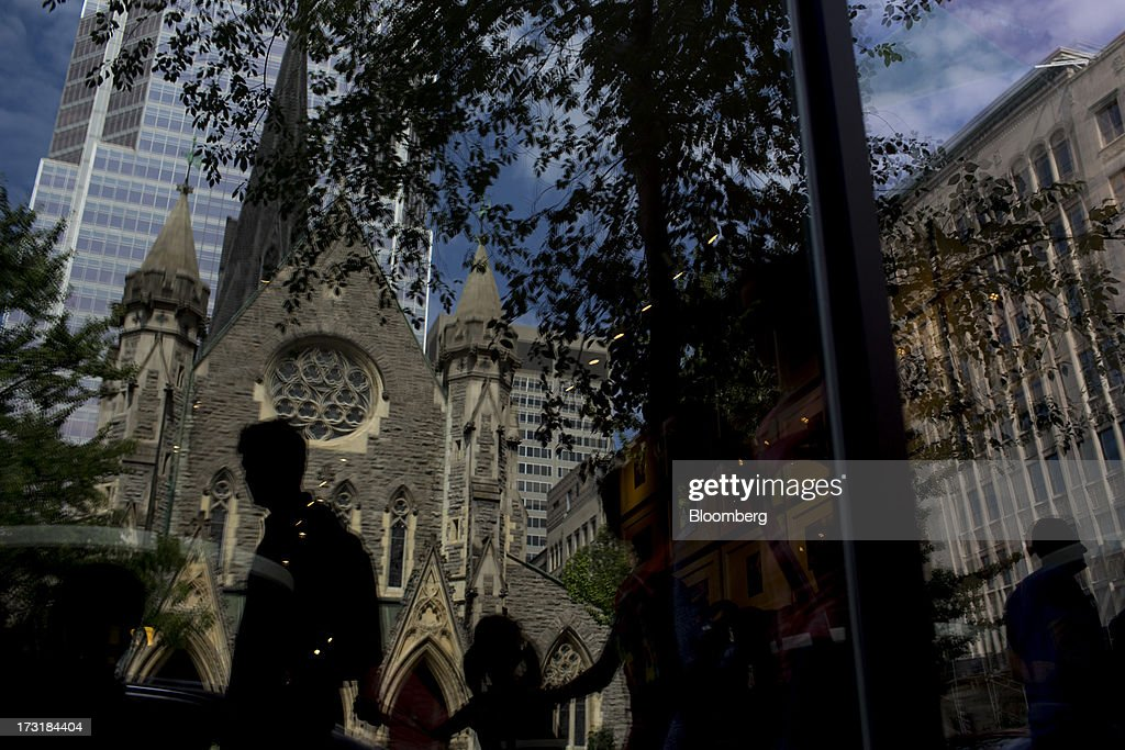 The reflection of people passing the St. James The Apostle Anglican Church is seen in a store window in Montreal, Quebec, Canada, on Monday, July 8, 2013. Montreals city council elected Laurent Blanchard as interim mayor to replace Michael Applebaum, who quit last week after being arrested on corruption charges. Photographer: Brent Lewin/Bloomberg via Getty Images