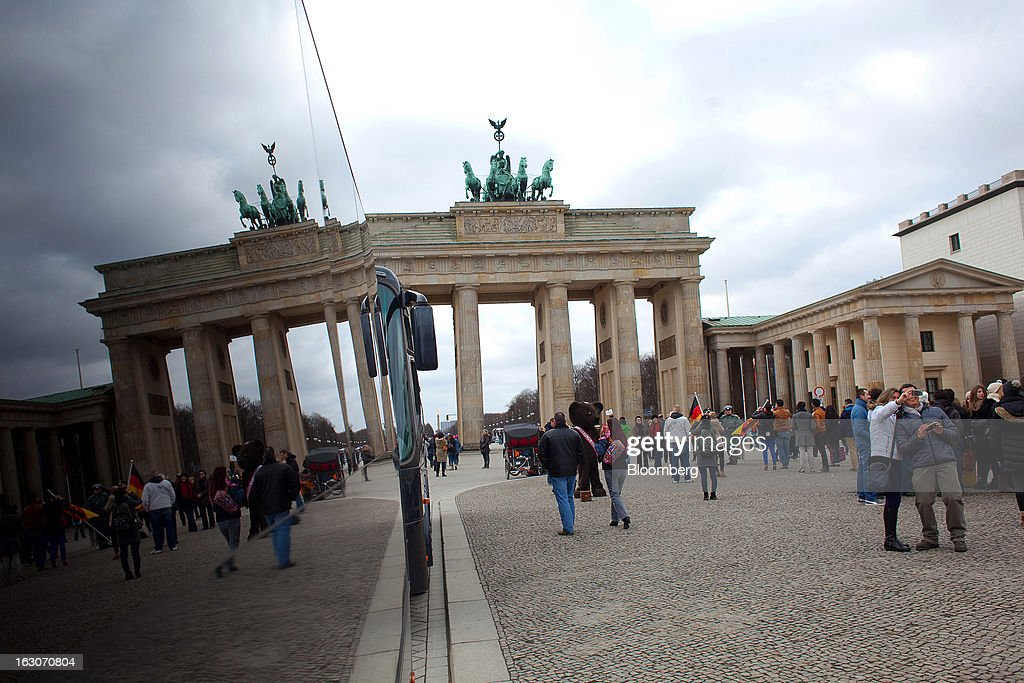 The reflection of the Brandenburg gate is seen on the side of a tourist bus in Berlin, Germany, on Sunday, March 3, 2013. Germany's 10-year government bonds advanced for a second day even before a report that economists said will show producer prices in the euro area increased for the first time in four months in January. Photographer: Krisztian Bocsi/Bloomberg via Getty Images