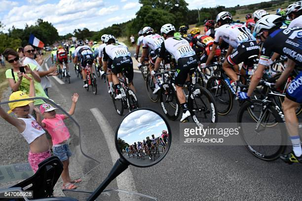 TOPSHOT The reflection of the pack riding is seen in the mirror of a motorcycle as fans cheer along the road during the 1625 km seventh stage of the...