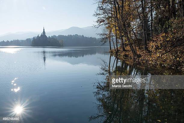 The reflection of the sun shines on Bled Lake on November 1 2015 in Bled Slovenia Bled Lake in the Julian Alps is known as one of the most enchanted...