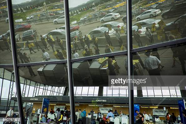 The reflection of United Continental Holdings Inc flight attendants are seen in a window while picketing for a new contract at Dulles International...