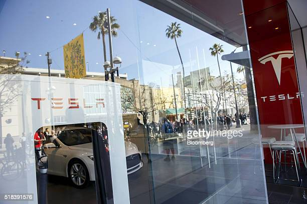 The reflections of customers are seen waiting in line ahead of the Model 3 announcement outside the Tesla Motors Inc store on the Third Street...