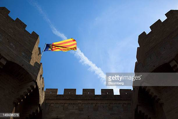 The regional flag of Valencia flies above the Torres de Serrano in Valencia Spain on Tuesday May 29 2012 The collapse of regional finances is pushing...