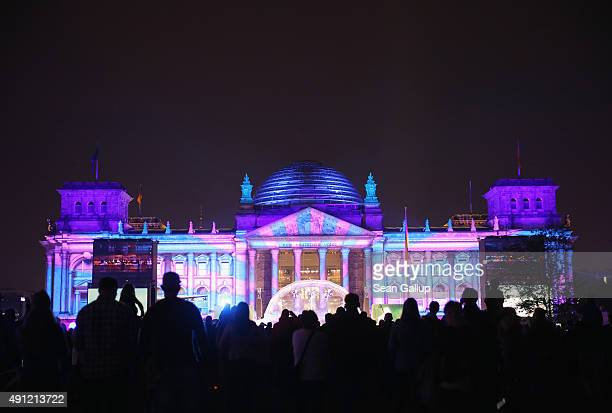 The Reichstag stands illuminated for performances during celebrations on the 25th anniversary of German reunification on October 3 2015 in Berlin...