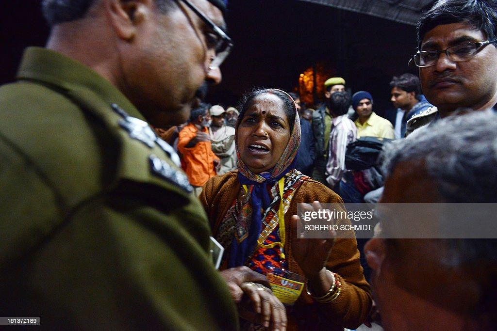 The relative of a traveller (C) that was killed during a stampede at the railway station in Allahabad, discusses with an Indian policemen on February 10, 2013. At least 10 people died in the stampede as pilgrims headed home from India's giant Kumbh Mela festival, which drew a record 30 million people to the banks of the river Ganges. The lives were lost at the main railway station where 10 corpses wrapped in white sheets could be seen on a train platform several hours after the incident which occurred in the early evening, an AFP photographer said.