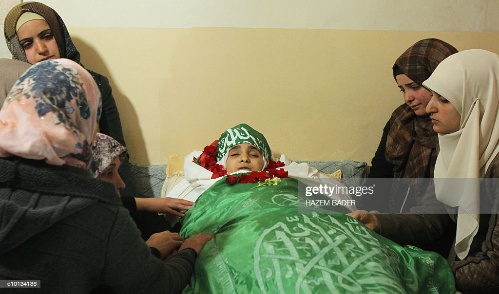 The relatives of Palestinian Kalzar al-Uweiwi, a Palestinian teenager who was killed a day earlier following a reported stabbing attack, mourn over her body ahead of her funeral, in the Israeli occupied West Bank city of Hebron, February 14, 2016. Israeli forces shot dead Kalzar al-Uweiwi, 17, as she tried to stab a soldier in the city of Hebron on February 13, according to Israeli and Palestinian authorities. BADER