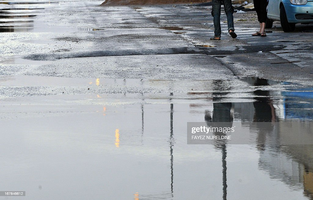 The relection of Saudis is seen on a puddle after heavy rains on May 1, 2013, in the north of the Saudi capital Riyadh. Sixteen people have died and three more are missing in Saudi Arabia after downpours caused flash floods in several areas of the desert kingdom, the civil defence authorities said.