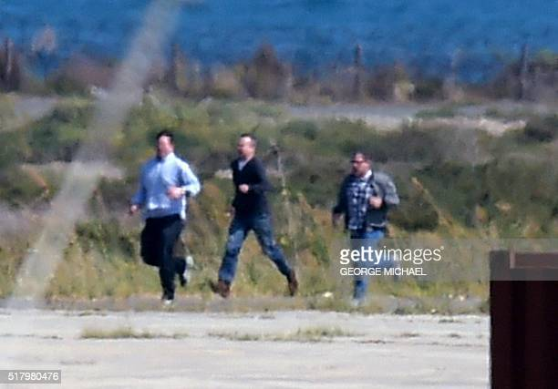 The remaining passengers on the hijacked EgyptAir Airbus A320 which was diverted to Cyprus run on the tarmac after leaving the plane as the hijacker...