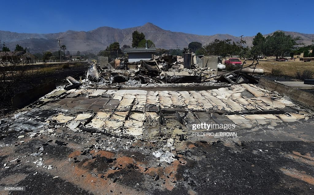 The remains from a demolished home in the community of Squirrel Valley in Lake Isabella, California on June 24, 2016. An intense wildfire broke out yesterday afternoon scorched dozens of homes and structures in this mountainous community northeast of Bakersfield in Kern County. / AFP / FREDERIC
