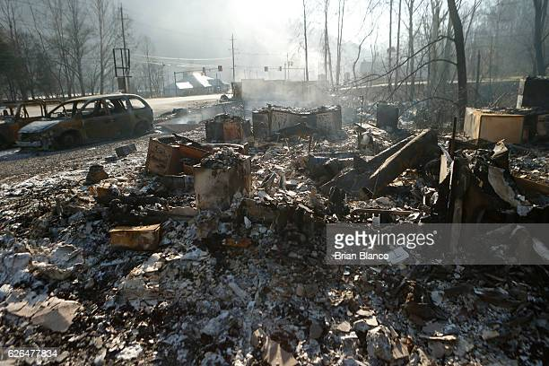 The remains of a business smolders after a wildfire November 29 2016 in Gatlinburg Tennessee Thousands of people have been evacuated from the area...