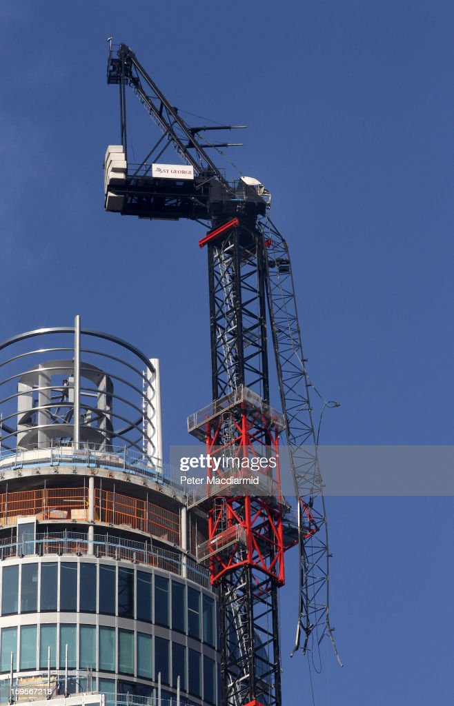 The remains of a construction crane hang from St Georges Wharf in Vauxhall, on January 16, 2013 in London, England. According to reports, a helicopter hit the crane on St Georges Wharf Tower before plunging into the road below during the morning rush hour.