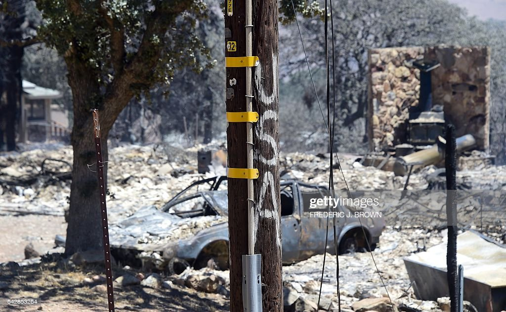 The remains of a demolished home with vehicle out front are seen in the community of Squirrel Valley in Lake Isabella, California on June 24, 2016. An intense wildfire broke out yesterday afternoon scorched dozens of homes and structures in this mountainous community northeast of Bakersfield in Kern County. / AFP / FREDERIC