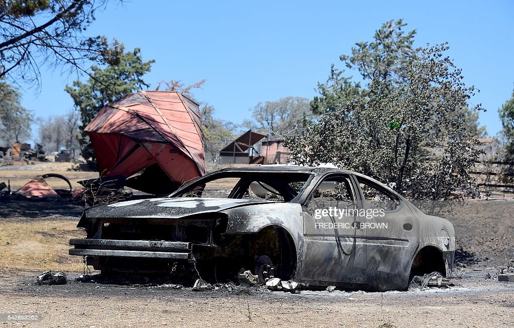 The remains of a demolished structure with vehicle out front are seen in the community of Squirrel Valley in Lake Isabella, California on June 24, 2016. An intense wildfire broke out yesterday afternoon scorched dozens of homes and structures in this mountainous community northeast of Bakersfield in Kern County. / AFP / FREDERIC