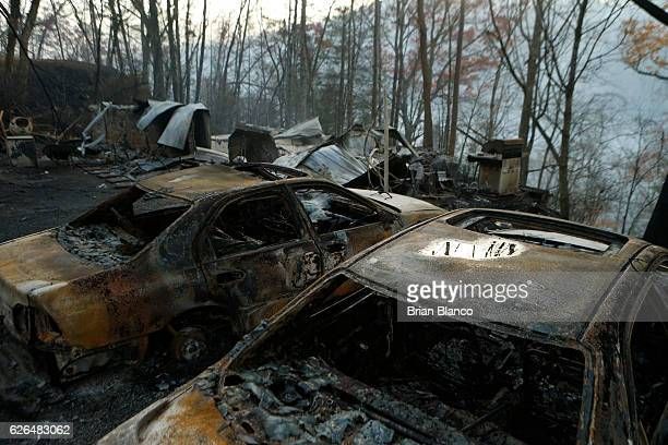 The remains of a home and cars smolder after a wildfire November 29 2016 in Gatlinburg Tennessee Thousands of people have been evacuated from the...