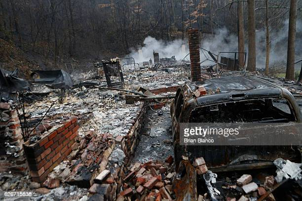 The remains of a home smolder in the wake of a wildfire November 30 2016 in Gatlinburg Tennessee Thousands of people have been evacuated from the...