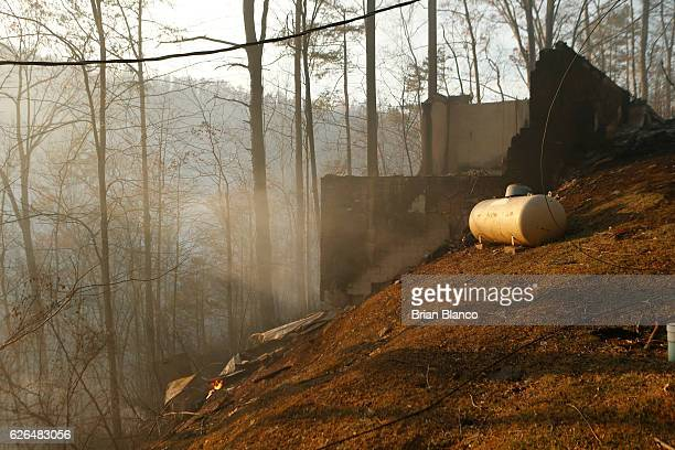 The remains of a home smolders after a wildfire November 29 2016 in Gatlinburg Tennessee Thousands of people have been evacuated from the area and...
