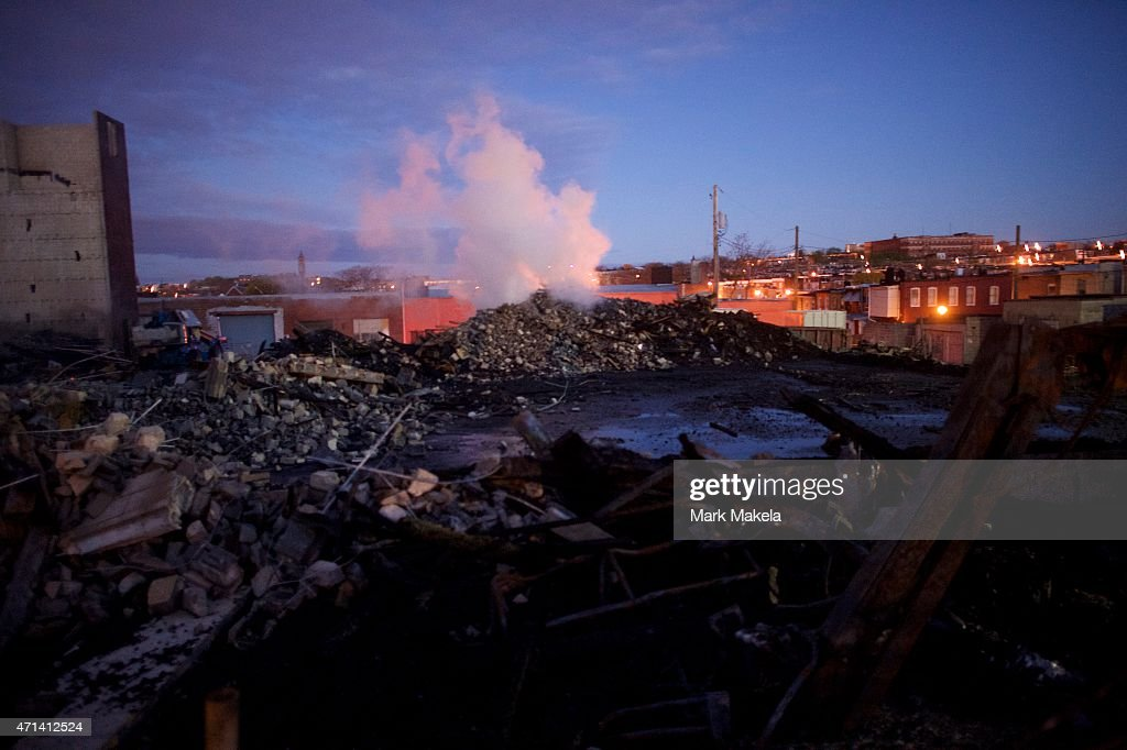 The remains of a senior center set ablaze during night riots smolder at dawn on April 28 2015 in Baltimore Maryland Freddie Gray was arrested for...
