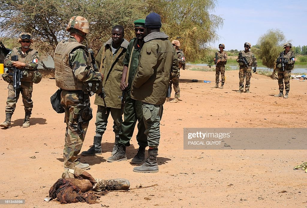CONTENT - The remains of a suicide bomber lay on the ground as French soldiers patrol at the site where the suicide bomber blew himself up on February 10, 2013 in northern Gao on the road to Gourem. Fighting between Islamists rebels and Malian soldiers broke out in the center of Gao, the largest city in northern Mali, recently taken over by the French military and Malian armed Islamist groups, hit by two suicide bombings in two days. AFP PHOTO / PASCAL GUYOT