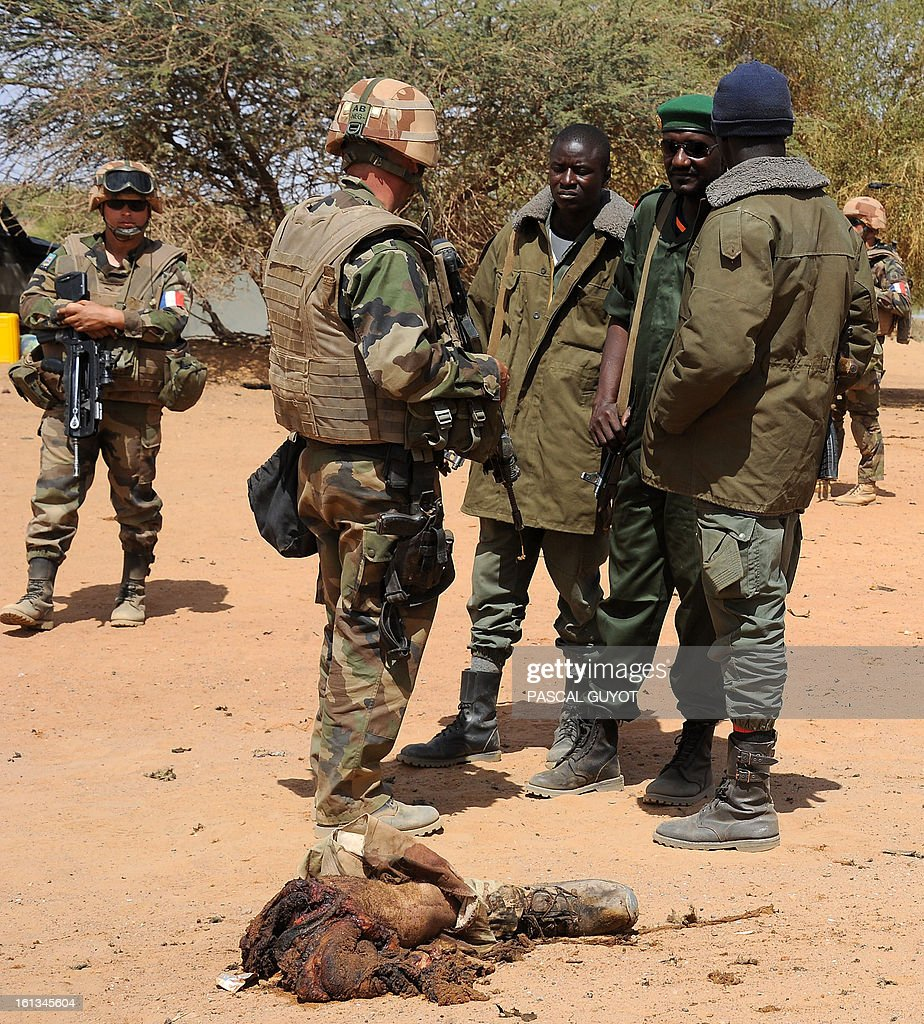 CONTENT - The remains of a suicide bomber lay on the ground as French soldiers patrol at the site where the suicide bomber blew himself up on February 10, 2013 in northern Gao on the road to Gourem. Fighting between Islamists rebels and Malian soldiers broke out in the center of Gao, the largest city in northern Mali, recently taken over by the French military and Malian armed Islamist groups, hit by two suicide bombings in two days.