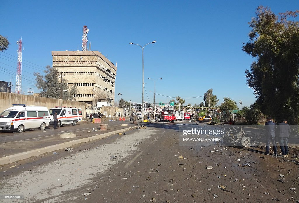 The remains of a vehicle (R) and a view of the police headquarters (L) are viewed after a car bombing followed by an assault by grenade-throwing gunmen on the police headquarters in a disputed northern city of Kirkuk, on February 3, 2013, killing some 30 people. The vehicle that was detonated in the center of the city was painted to appear as though it was a police car, and the militants who sought to seize the compound were dressed as policemen, witnesses said. AFP PHOTO/MARWAN IBRAHIM