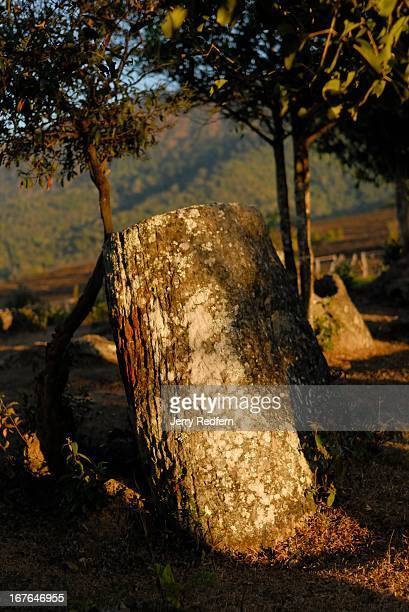 The remains of an ancient stone jar catch the last rays of the day at Site Two of the Plain of Jars Many of the massive jars at the site have been...