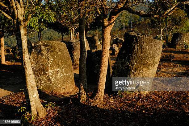 The remains of ancient stone jars catch the last rays of the day at Site Two of the Plain of Jars Many of the massive jars at the site have been...