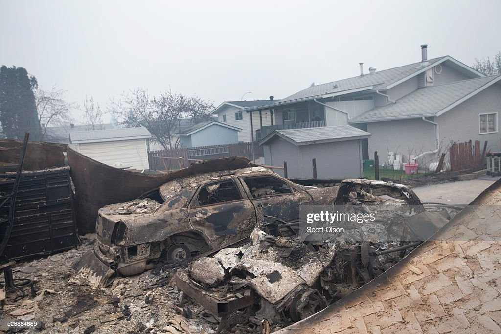 The remains of charred vehicles sit in a residential neighborhood heavily damages by a wildfire on May 7 2016 in Fort McMurray Alberta Canada...