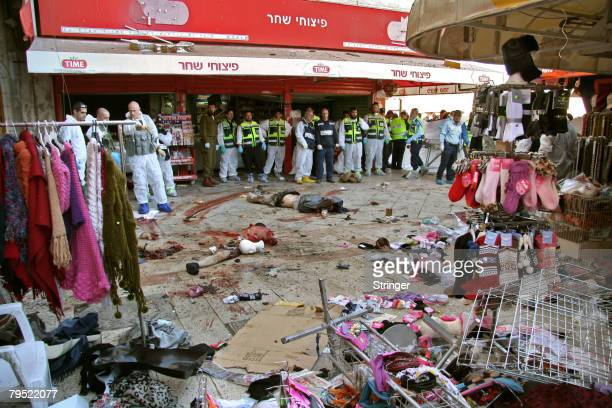 The remains of two Palestinian militants lie amongst the devastation at the scene of a double suicide bombing attempt February 4 2008 in the southern...