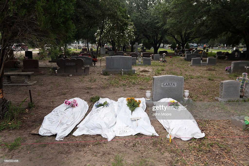 The remains of unidentified immigrants lie in a cemetery after being exhumed on May 21, 2013 in Falfurrias, Texas. Teams from Baylor University and the University of Indianapolis are exhuming the bodies of more than 50 immigrants who died, mostly from heat exhaustion, while crossing illegally from Mexico into the United States. The bodies will be examined and cross checked with DNA sent from Mexico and Central American countries, with the goal of reuniting the remains with families. In Brooks County alone, at least 129 immigrants perished in 2012, the highest rate in the United States, according to forensic anthropologists.