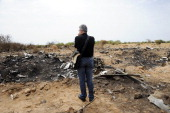 The representative of the Lebanese victims' relatives looks at debris at the crash site of the Air Algerie Flight AH 5017 in Mali's Gossi region west...