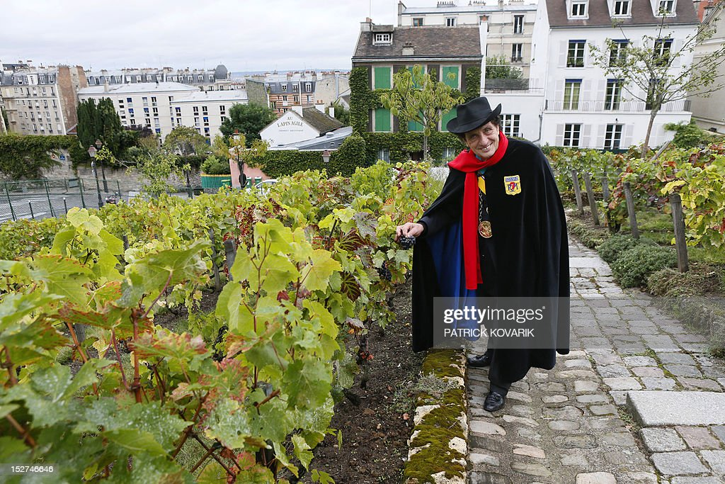 The 'Republic of Montmartre President' Alain Coquard, wearing a red scarf, black cape and hat, the famous outfit of Aristide Bruant, immortalized by French artist Toulouse-Lautrec, poses on September 25, 2012 in the vineyard of Montmartre located next to the Sacre Coeur Basilica and the Lapin Agile cabaret. Founded on May 7, 1921, by famous artists as French illustrator Francisque Poulbot who lived in Montmartre, the Republic of Montmartre organizes charity programs and cultural actions. AFP PHOTO / PATRICK KOVARIK