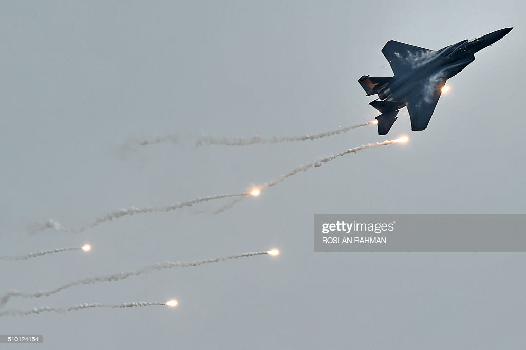 The Republic of Singapore Air Force (RSAF) McDonnell Douglas F-15SG fighter jet releases flares during aerial display preview at the Singapore Airshow at Changi exhibition center in Singapore on February 14, 2016. The Singapore Airshow 2016 begins on February 16 to 21. AFP PHOTO / ROSLAN RAHMAN / AFP / ROSLAN RAHMAN