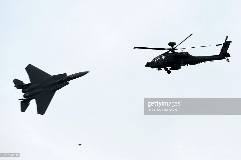 The Republic of Singapore Air Force (RSAF) McDonnell Douglas F-15SG (L) fighter jet and a Sikorsky AH-64 attack helicopter (R) crosses over during a preview at the Singapore Airshow at Changi exhibition center in Singapore on February 14, 2016. The Singapore Airshow 2016 begins on February 16 to 21. AFP PHOTO / ROSLAN RAHMAN / AFP / ROSLAN RAHMAN