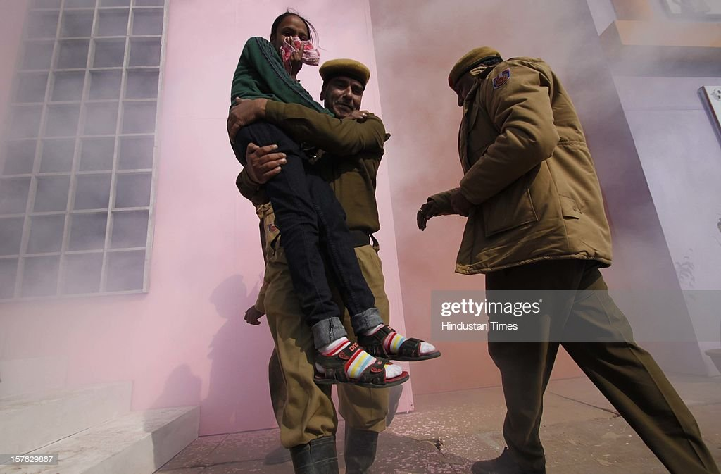 The rescue team carrying out a girl pretend to be injured during a mock drill session at Burari ground on December 4,2102 in New Delhi, India. Mock Drill performs at various place in the capital to test the alertness and responds during the time of emergency situation such as Earthquake, Fire, Bomb Blast.