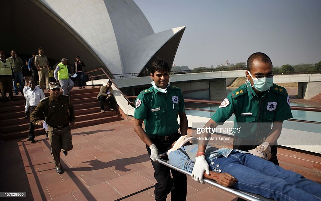 The rescue team carrying out a man pretend to be injured during a mock drill session at the Lotus Temple on December 4, 2012 in New Delhi, India. A mock drill held in the capital under which simulated situations was created across the city to check medical response system of prominent hospitals in the city in the event of an earthquake, fire and bomb blasts.