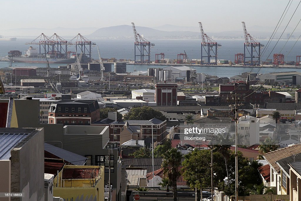 The residential district of Woodstock overlooks gantry cranes on the harbourside in the commercial port area of Cape Town, South Africa, on Wednesday, April 24, 2013. South Africa's gross domestic product is forecast to expand 2.6 percent this year, compared with 2.5 percent in 2012, according to the country's central bank. Photographer: Nadine Hutton/Bloomberg via Getty Images
