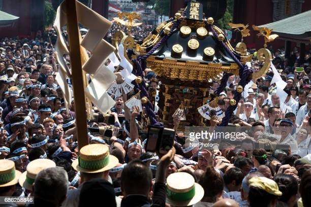 The residents of Asakusa band together to carry a 'mikoshi' while they chant together during the Sanja Festival in front of in Sensoji Temple in...