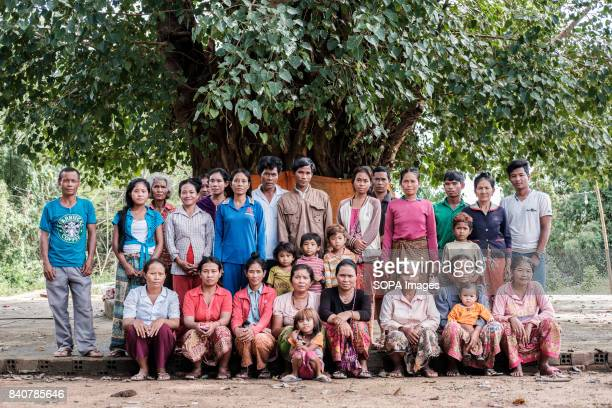 The residents of Kbal Romeas village pose in front of a sacred tree that stands at the center of the village They refused to take the compensation...