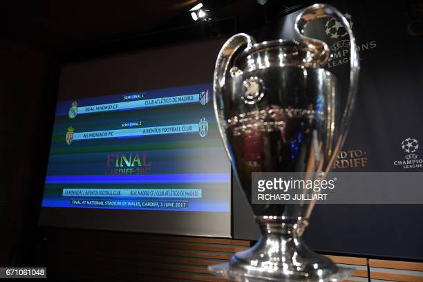 The result of the UEFA football Champion's league draw semifinals is displayed on a screen near the trophy on April 21 2017 in Nyon / AFP PHOTO /...