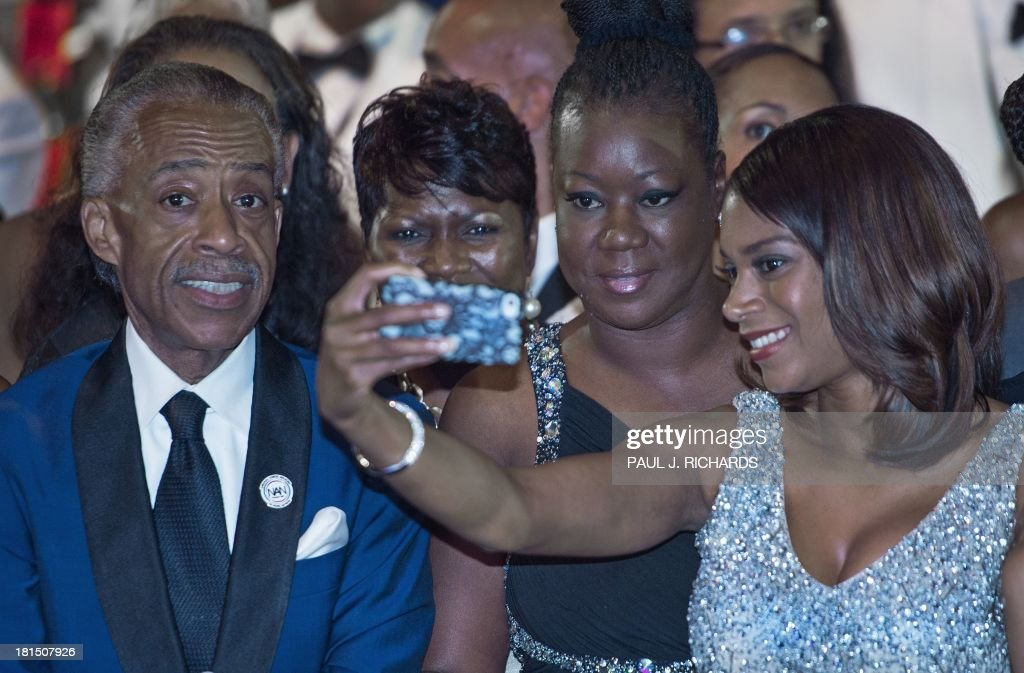 The Rev. Al Sharpton(L) 58-yrs smiles as his girlfriend Aisha McShaw, (R) 35-yrs, takes a photo including Sybrina Fulton (3rd from L), the late Trayvon Martin's mother after listening to US President Barack Obama deliver remarks at the Congressional Black Caucus Foundation, Inc. (CBCF) Annual Phoenix Awards September 21, 2013 at the Washington Convention Center in Washington, DC. The woman 2nd from L is unidentified. AFP Photo/Paul J. Richards