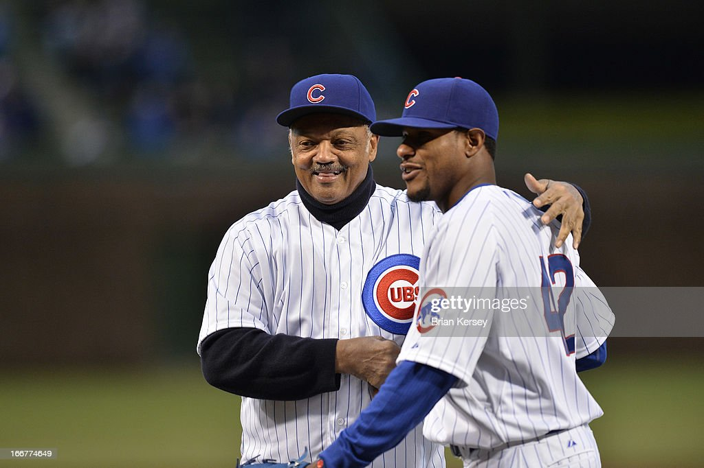 The Rev. Jesse Jackson Sr. (L) shakes hands with Edwin Jackson of the Chicago Cubs after throwing out a ceremonial first pitch to him before the game against the Texas Rangers at Wrigley Field on April 16, 2013 in Chicago, Illinois. All uniformed team members are wearing jersey number 42 in honor of Jackie Robinson Day.