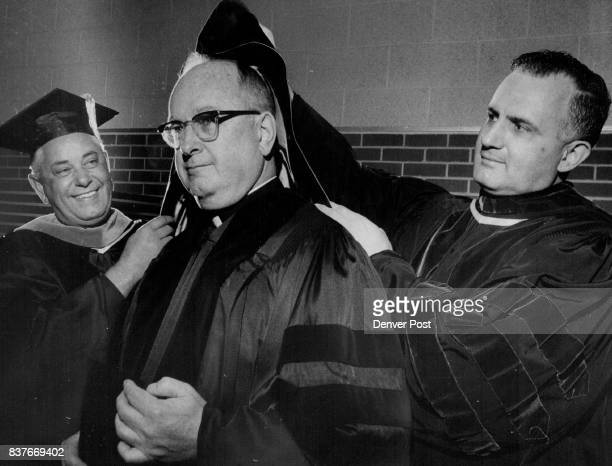 The Rev Robert F Houlihan right dean of students helps the Very Rev Louis G Mattione president left put a doctor of laws hood on the former president...