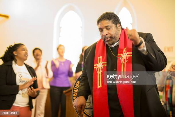 The Rev William J Barber II joins in song at the conclusion of a press conference held by the state NAACP at Davie Street Presbyterian Church in...