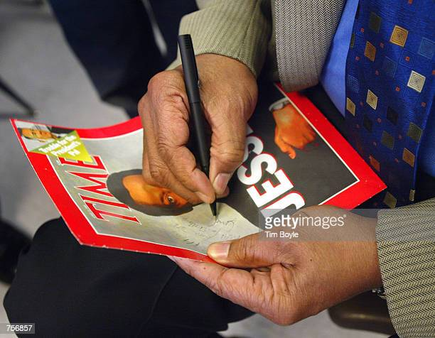 The Reverend Jesse Jackson autographs a cover of TIME magazine during a visit to Faraday Elementary Schoola April 4 2002 in Chicago IL Jackson...