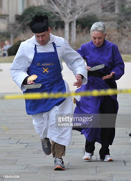 The Reverend Matthew Hanisian of St Albans Parish heads to the finish line as his competition stops to pick up their pancakes February 21 2012 during...