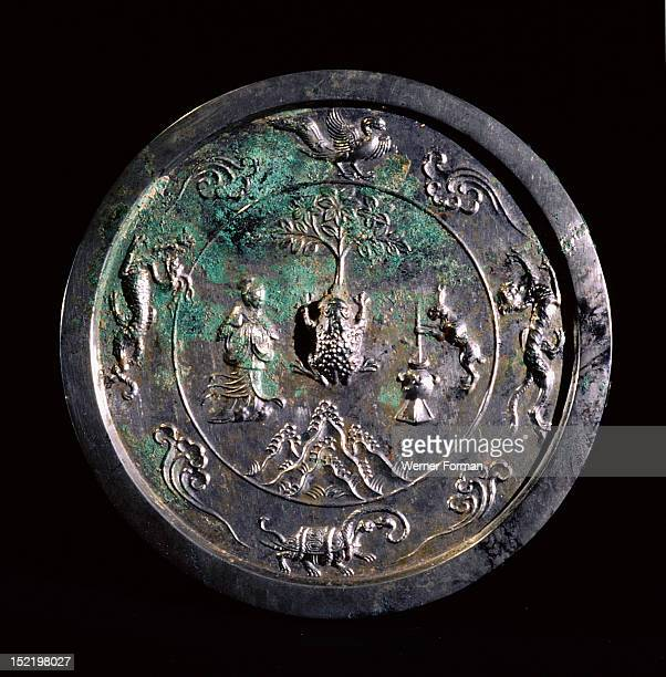 The reverse side of a mirror In the outer rim are the animals of the four quarters the tortoise of the north the dragon of the east the bird of the...